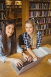 Estudiante sonriente que trabaja en la biblioteca Imagenes de archivo