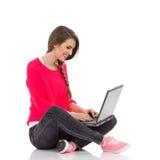 Estudiante sonriente que usa el ordenador portátil Fotografía de archivo