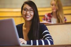 Estudiante sonriente que usa el ordenador portátil durante clase Imagenes de archivo