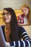 Estudiante sonriente que usa el ordenador portátil durante clase Fotos de archivo libres de regalías