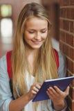Estudiante sonriente que usa la tableta en el vestíbulo Imagen de archivo libre de regalías