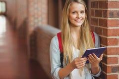 Estudiante sonriente que usa la tableta en el vestíbulo Imágenes de archivo libres de regalías