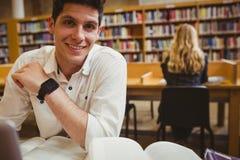 Estudiante sonriente que usa su ordenador portátil mientras que trabaja fotos de archivo