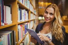 Estudiante sonriente que usa su tableta imagenes de archivo