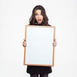 Estudiante sorprendente que lleva a cabo al tablero en blanco Imagen de archivo libre de regalías