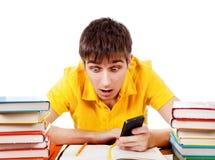 Estudiante sorprendido con un teléfono Foto de archivo libre de regalías