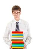 Estudiante sorprendido que sostiene la pila de los libros Fotos de archivo