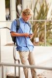 Estudiante Standing Outside Building de la High School secundaria con el teléfono Imagen de archivo libre de regalías