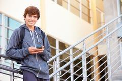 Estudiante Standing Outside Building de la High School secundaria con el teléfono Fotografía de archivo libre de regalías