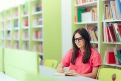 Estudiante Studying y notas el tomar en la biblioteca Foto de archivo