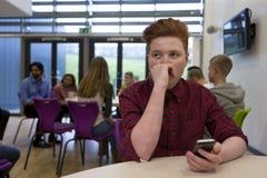 Estudiante subrayado con Smartphone Imágenes de archivo libres de regalías