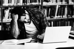 Estudiante subrayado Doing His Homework en el escritorio Foto de archivo libre de regalías