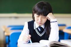 Estudiante subrayado Of High School que se sienta en sala de clase Imagen de archivo libre de regalías