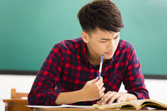 Estudiante subrayado que estudia para el examen en sala de clase Foto de archivo