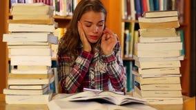 Estudiante subrayado que estudia y que toma notas en la biblioteca rodeada por los libros