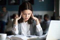 Estudiante subrayado que tiene dolor de cabeza que se prepara para el examen de la prueba en café Imagen de archivo