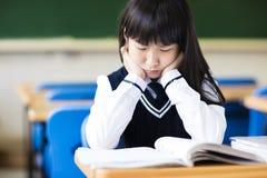 Estudiante subrayado Sitting en sala de clase Fotos de archivo libres de regalías