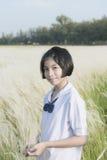 Estudiante tailandesa con el prado de la flor blanca imagen de archivo libre de regalías
