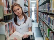 Estudiante tailandesa en uniforme que lee un libro en biblioteca Fotografía de archivo libre de regalías