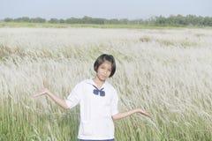Estudiante tailandesa l con el prado de la flor blanca foto de archivo libre de regalías