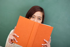 Estudiante trabajador que mira sobre t su libro Foto de archivo libre de regalías
