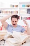 Estudiante trastornado con la mano en su cabeza rodeada por los libros Imagenes de archivo