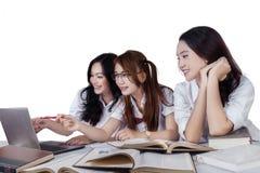 Estudiante tres que estudia en el escritorio Imagen de archivo