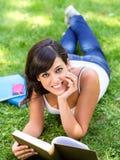 Estudiante trigueno con el libro en hierba Foto de archivo libre de regalías