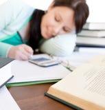 Estudiante trigueno que hace su preparación en un escritorio Imagenes de archivo