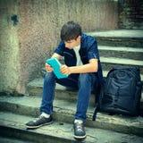 Estudiante triste con el libro Imagen de archivo libre de regalías