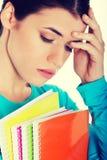 Estudiante triste con el libro de trabajo Imagen de archivo