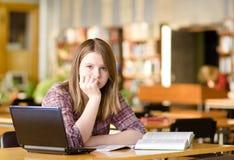 Estudiante triste con el ordenador portátil que trabaja en biblioteca Imagen de archivo