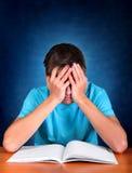 Estudiante triste con un libro Foto de archivo libre de regalías