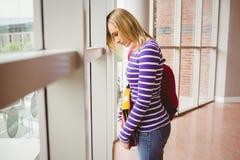 Estudiante triste por la ventana en universidad Imágenes de archivo libres de regalías