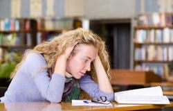 Estudiante triste que trabaja en biblioteca Fotografía de archivo