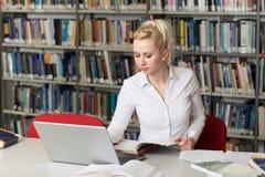 Estudiante Typing en el ordenador portátil en la biblioteca de universidad Foto de archivo libre de regalías
