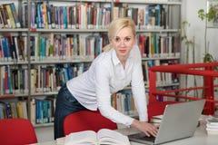 Estudiante Typing en el ordenador portátil en la biblioteca de universidad Imagen de archivo