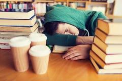 Estudiante u hombre cansado con los libros en biblioteca Imágenes de archivo libres de regalías