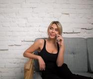 Estudiante u hombre de negocios sonriente de mujer que habla en el teléfono móvil mientras que se sienta en un sofá Imagen de archivo