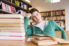 Estudiante u hombre joven aburrido con los libros en biblioteca Foto de archivo