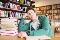 Estudiante u hombre joven aburrido con los libros en biblioteca Fotografía de archivo libre de regalías