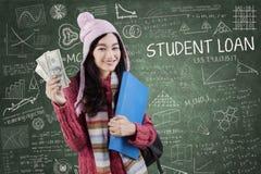 Estudiante universitaria con el dinero en clase Foto de archivo