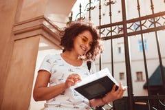 Estudiante universitaria hermosa que lee un libro al aire libre Aprendizaje elegante de moda del estudiante de mujer Fotografía de archivo