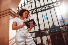 Estudiante universitaria hermosa que lee un libro al aire libre Estudiante del adolescente que aprende en la yarda de la universi Imagen de archivo
