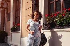 Estudiante universitaria hermosa que sostiene un libro y que escucha la música por los groupmates que esperan de la universidad Imágenes de archivo libres de regalías