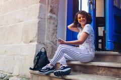Estudiante universitaria joven hermosa que usa el teléfono elegante y escuchando la música que se sienta por el café Fotos de archivo