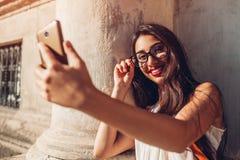 Estudiante universitaria joven que toma el selfie en la calle de la ciudad Mujer de Oriente Medio feliz que usa el teléfono al ai Fotos de archivo
