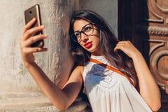 Estudiante universitaria joven que toma el selfie en la calle de la ciudad Mujer de Oriente Medio feliz que usa el teléfono al ai Fotos de archivo libres de regalías