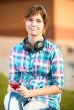 Estudiante universitaria joven sonriente que manda un SMS en un teléfono celular Imagen de archivo