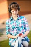 Estudiante universitaria joven sonriente que manda un SMS en un teléfono celular Fotos de archivo libres de regalías